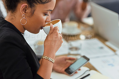 Buy stock photo Shot of a businesswoman using a cellphone while drinking coffee in an office