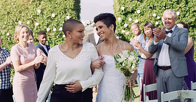 Buy stock photo Cropped shot of an affectionate young lesbian couple leaving their wedding venue with their guests clapping in the background