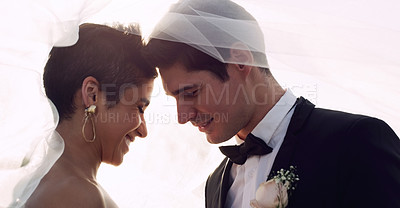 Buy stock photo Cropped shot of an affectionate young newlywed couple smiling while covering themselves with a veil on their wedding day