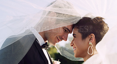 Buy stock photo Cropped shot of an affectionate young newlywed couple sharing an intimate moment while covering themselves with a veil on their wedding day