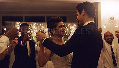 Buy stock photo Cropped shot of an affectionate young newlywed couple dancing while their guests are holding up sparklers at their wedding reception