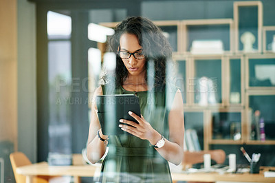Buy stock photo Shot of a young businesswomen using a digital tablet in a modern office