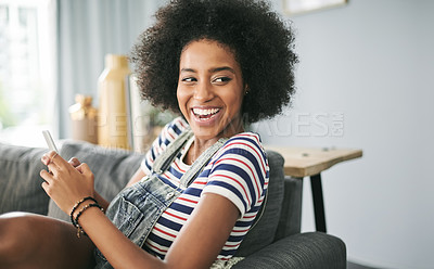 Buy stock photo Shot of an attractive young woman using a cellphone while relaxing at home