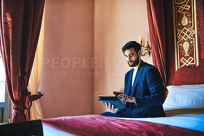 Buy stock photo Shot of a handsome young businessman sitting on a bed and using a digital tablet inside his hotel room