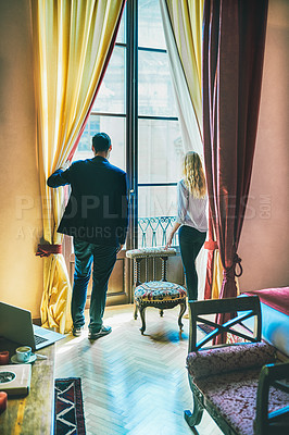 Buy stock photo Rearview shot of two young businesspeople looking out the window of their hotel room