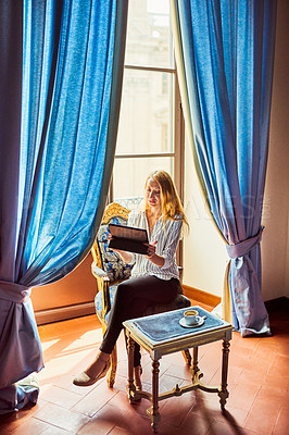 Buy stock photo Full length shot of an attractive young businesswoman sitting down and using a digital tablet inside her hotel room