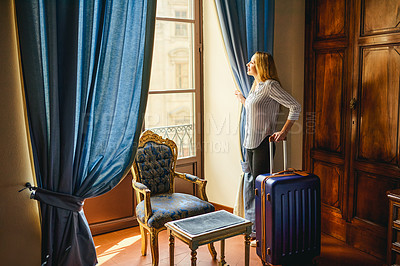 Buy stock photo Full length shot of a young businesswoman standing with her suitcase and looking out the window inside her hotel room