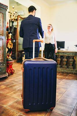Buy stock photo Shot of a suitcase at the reception area of a hotel with two businesspeople shaking hands in the background