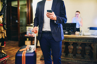 Buy stock photo Cropped shot of a businessman standing with his luggage and using his cellphone at the reception area of a hotel