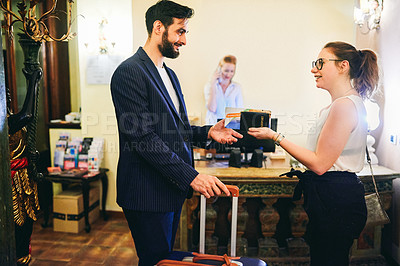 Buy stock photo Shot of two young businesspeople meeting up and chatting at the reception area of a hotel