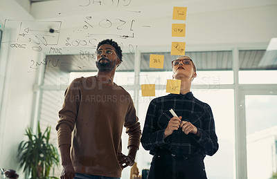 Buy stock photo Shot of two businesspeople brainstorming with notes on a glass wall in an office