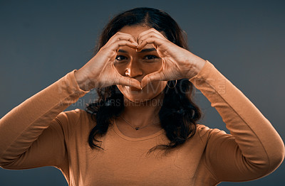 Buy stock photo Studio portrait of an attractive young woman showing the love sign while standing against a grey background