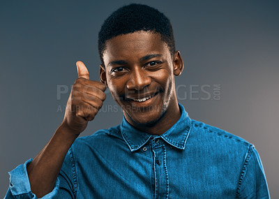 Buy stock photo Studio portrait a handsome young man showing thumbs up while standing against a grey background