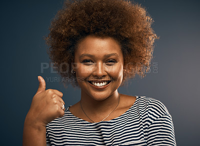 Buy stock photo Studio portrait of an attractive young woman showing thumbs up while standing against a grey background