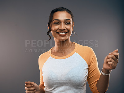 Buy stock photo Studio portrait of an attractive young woman dancing while standing against a grey background