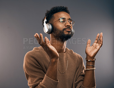 Buy stock photo Studio shot of a handsome young man listening to music on his headphones while standing against a grey background