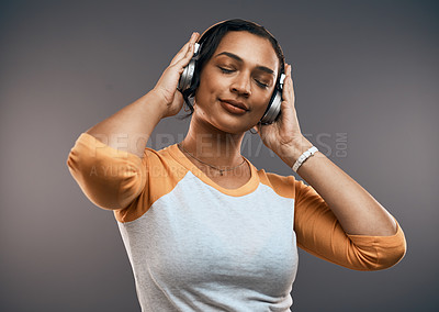 Buy stock photo Studios shot of an attractive young woman listening to music on her headphones while standing against a grey background