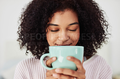 Buy stock photo Cropped shot of an attractive young woman sitting and holding a cup of coffee during a day off at home