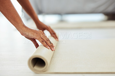 Buy stock photo Cropped shot of a woman rolling out her yoga mat at home
