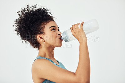 Buy stock photo Studio shot of a young woman drinking water while working out against a grey background