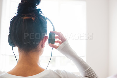 Buy stock photo Rearview shot of a young woman listening to music through her headphones