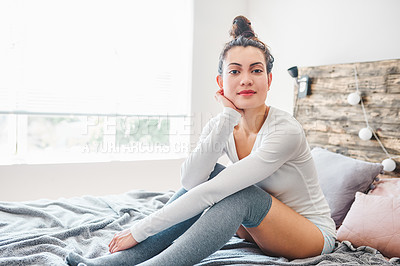 Buy stock photo Shot of a beautiful young woman sitting on her bed