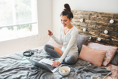 Buy stock photo Shot of a young woman holding a credit card while browsing online on her laptop