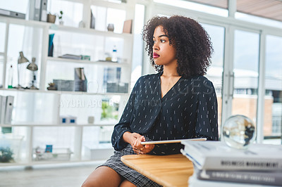 Buy stock photo Cropped shot of an attractive young businesswoman sitting alone in her office and looking contemplative while holding a tablet