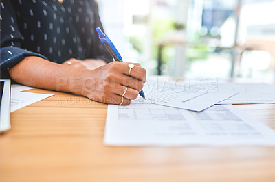 Buy stock photo Cropped shot of an unrecognizable businesswoman sitting alone in the office and writing on documents