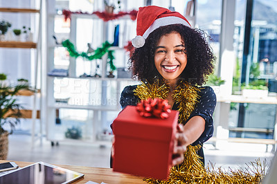 Buy stock photo Cropped shot of an attractive young businesswoman sitting alone in the office and holding out a christmas present