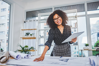 Buy stock photo Portrait of a young businesswoman using a digital tablet while working with blueprints in an office