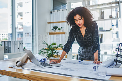 Buy stock photo Shot of a young businesswoman using a laptop while working with blueprints in an office