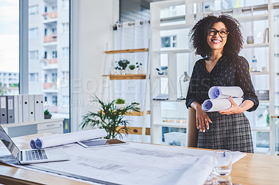 Buy stock photo Shot of a young businesswoman looking thoughtful while working with blueprints in an office
