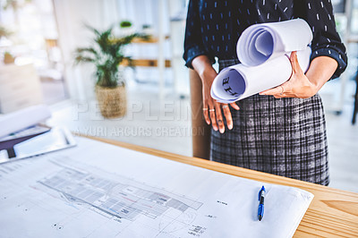 Buy stock photo Closeup shot of an unrecognisable businesswoman working with blueprints in an office