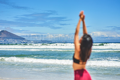 Buy stock photo Rearview shot of a young woman meditating at the beach