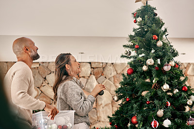 Buy stock photo Cropped shot of a cheerful middle aged couple placing decorations on a Christmas tree inside at home during the day