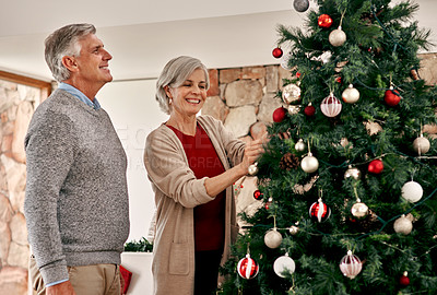 Buy stock photo Cropped shot of a cheerful mature couple placing decorations on a Christmas tree inside at home  during the day