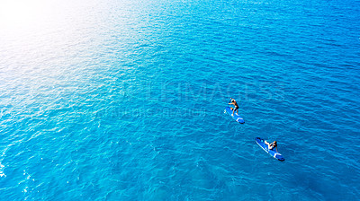Buy stock photo Shot of a man and woman paddle boarding across the sea