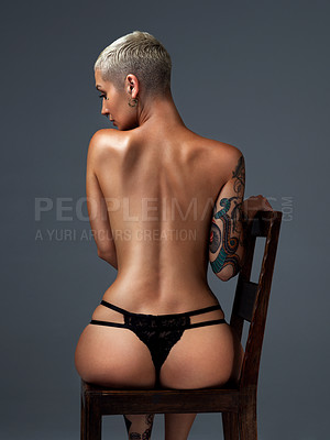 Buy stock photo Rearview shot of a beautiful young woman posing nude on a chair in the studio