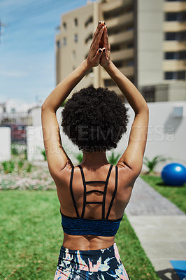 Buy stock photo Rearview shot of a young woman meditating in her backyard