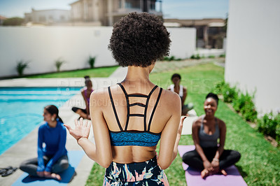 Buy stock photo Shot of a young woman giving a yoga class in a garden