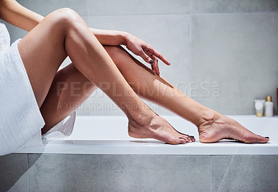Buy stock photo Cropped shot of an unrecognizable woman seated on the side of a bath exposing her legs inside of a bathroom in the morning