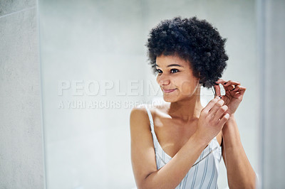 Buy stock photo Cropped shot of a cheerful young woman playing around with her hair while looking into a mirror inside of a bathroom in the morning