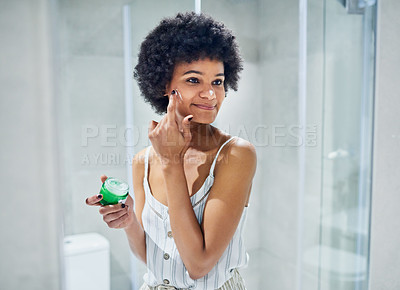 Buy stock photo Cropped shot of a cheerful young woman applying skin moisturizer to her face while looking into a mirror inside of a bathroom