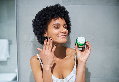 Buy stock photo Cropped shot of a cheerful young woman holding a tub of skin moisturizer to apply it on her face inside of a bathroom during the morning hours