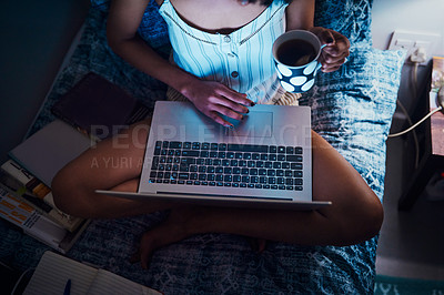 Buy stock photo High angle shot of an unrecognizable woman sitting and holding a cup of tea while using a laptop at home