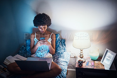 Buy stock photo Cropped shot of an attractive young woman sitting on her bed at home and using technology at night