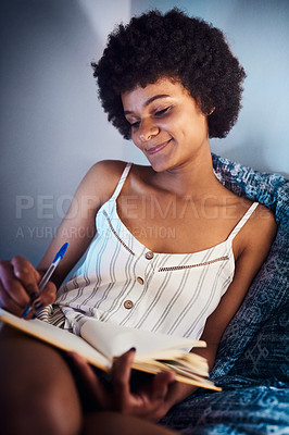 Buy stock photo Cropped shot of an attractive young woman sitting on her bed at home and writing in her notebook at night