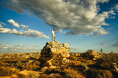 Buy stock photo Shot of a young man taking photos while standing on a cliff in a rural landscape