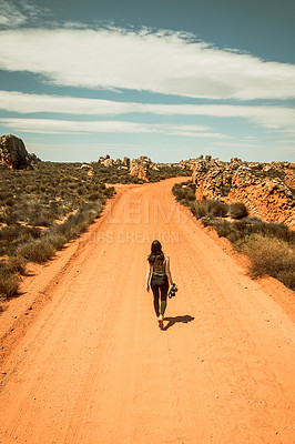 Buy stock photo Rearview shot of a young woman holding a camera while walking on a dirt road in a rural landscape